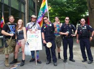 """Alguns movimentos LGBT nos EUA pregam o livre acesso às armas e ao porte legal de armas, com uma placa dizendo: """"Gays armados não são espancados""""."""