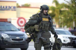 Um membro da SWAT chegando ao local do ataque.